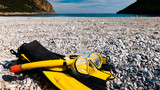 Flippers and snorkeling tube on sea shore - 205440699