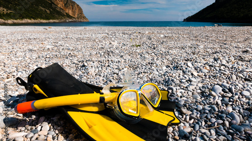 Foto Murales Flippers and snorkeling tube on sea shore