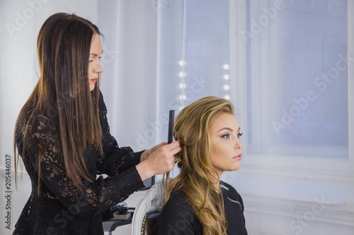 Fotobehang Kapsalon Professional hairdresser, stylist combing hair of female client in white make up room. Beauty and haircare concept
