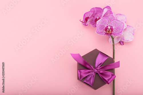 Fototapeta Pink orchid flowers and hexagonal gift box with bow. Flat layout