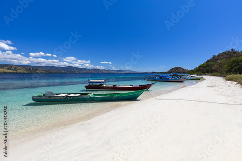 Boats on a white sand beach on a large Island in the Seventeen Island National Park, Flores, Indonesia.