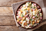 Hawaiian food: salad with pasta, ham, pineapple, onion, cheddar cheese with mayonnaise close-up in a bowl. horizontal top view - 205472411