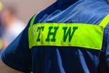 German technical emergency service sign on a vest from a man. THW, Technisches Hilfswerk means technical emergency service.