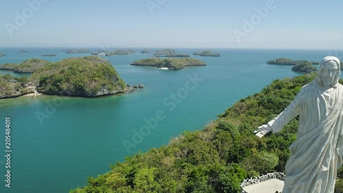 Statue of Jesus Christ on Pilgrimage island in Hundred Islands National Park, Pangasinan, Philippines. Aerial view of group of small islands with beaches and lagoons, famous tourist attraction