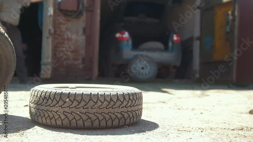 Rolling tire on the ground in front of car garage