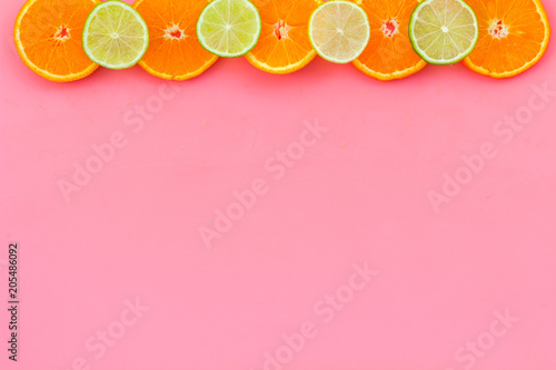 Citrus frame. Oranges and lime round slices composition on pink background top view copy space