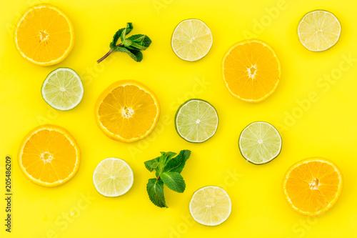 Wzór owoców. Pomarańcze i wapno round pokrajać skład na żółtego tła odgórnym widoku