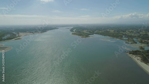 Aerial view of river flowing into the sea on the island Luzon, Philippines. Seascape, ocean and beautiful beach. Panorama of the tropical island.