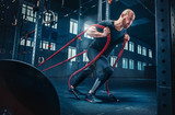 Men with battle rope battle ropes exercise in the fitness gym. CrossFit. - 205504029