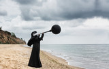 Plague doctor blows black balloon. Outdoor portrait with dramatic sky in background. - 205508066