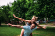 Quadro Piggybacking with spread hands. Two sports people having fun in the park.