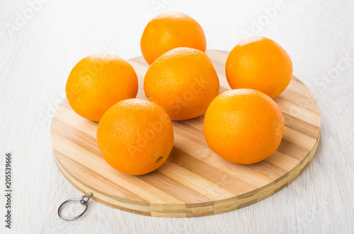 Ripe oranges on round striped cutting board on table