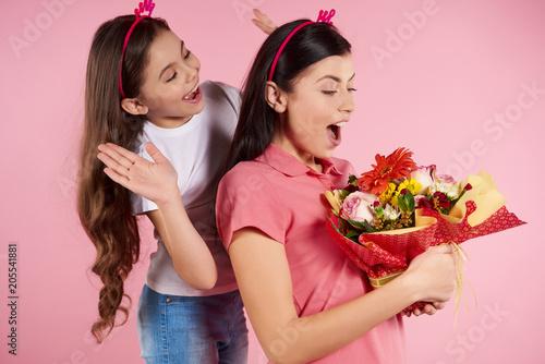 Ładna mała córka daje kwiaty pięknym