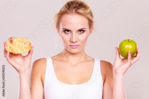 Poster Woman holds cake and fruit in hand choosing
