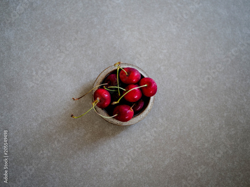 Foto Murales Fresh red cherries, in a ceramic bowl, on a gray background