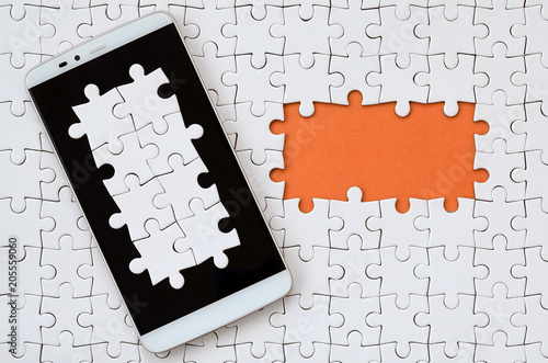 A modern big smartphone with several puzzle elements on the touch screen lies on a white jigsaw puzzle in an assembled state with missing elements