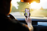 Driver uses navigation on his mobile phone in the car