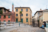 The old stone Saint Michele bridge in Vicenza with some houses and a view of the medieval clock tower in the background - 205564221