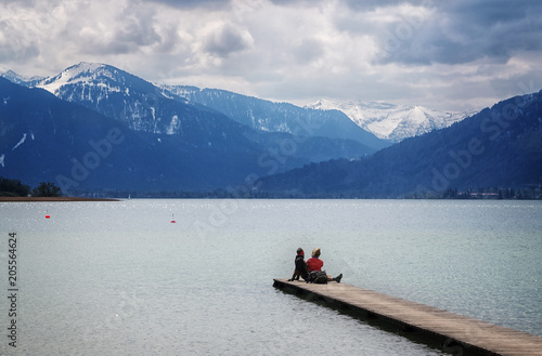 Acrylglas Pier Young woman and young man sitting together on the jetty in the tegernsee lake and looking at the blue mountains in the famous tourist resort of the Bavarian Alps, Bavaria, Germany, Europe,