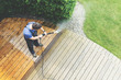Leinwandbild Motiv man cleaning terrace with a power washer - high water pressure cleaner on wooden terrace surface
