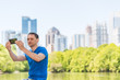Young man sitting taking selfie in Piedmont Park in Atlanta, Georgia with scenic water, and cityscape skyline of urban city skyscrapers downtown, Lake Clara Meer