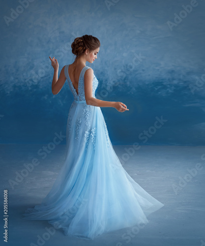 A young blonde girl is spinning in a luxurious blue dress with an open back. The background is a sky-blue wall. Beautiful, elegant, high hairstyle with weaving. Evening image