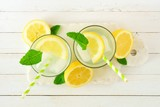 Summer lemonade in two glasses. Top view on a server against white wood.