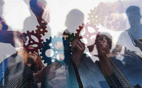 Fototapeta Business team connect pieces of gears. Teamwork, partnership and integration concept. double exposure