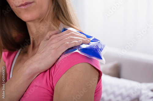 Woman Applying Ice Bag On Her Shoulder