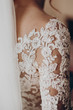 stylish bride detail, luxury lace gown on shoulder and red hair curl with veil, beautiful wedding dress. rustic wedding morning preparation. bridal getting ready. emotional moment. space for text