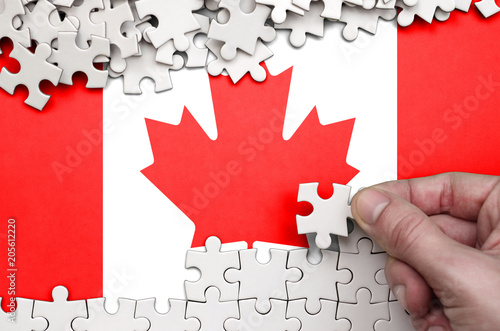 Canada flag is depicted on a table on which the human hand folds a puzzle of white color
