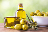 bowl of olives and bottle of extra virgin oil on background