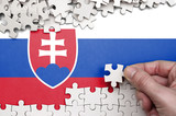 Slovakia flag  is depicted on a table on which the human hand folds a puzzle of white color
