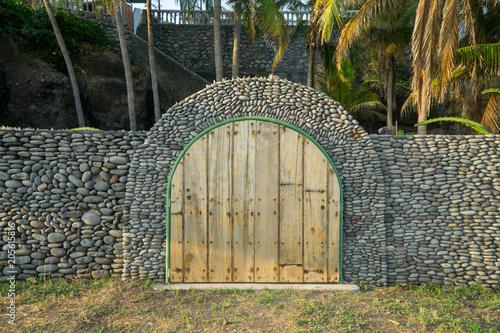 Drewniany drzwi i kamienna ściana przy plażą przy zmierzchem.
