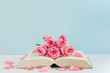 Quadro Vintage pink rose flowers with book on white and blue wooden background