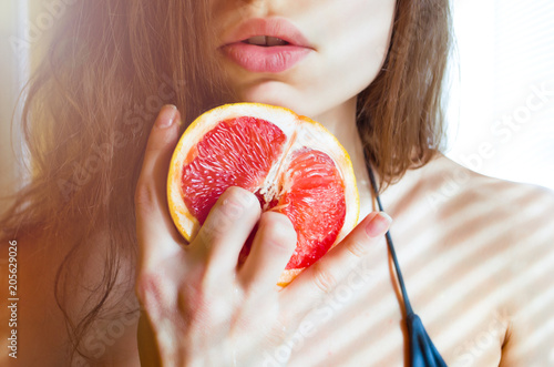 beautiful young sexy woman in bikini holding two fingers on grapefruit  on the background of her lips. Sex concept. - 205629026