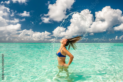 Woman splashing water with hair in the ocean