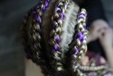 spit with kanekalon, fashionable youth hairstyle on the head of a girl close-up, purple kanekalon, colored hair, thick braids