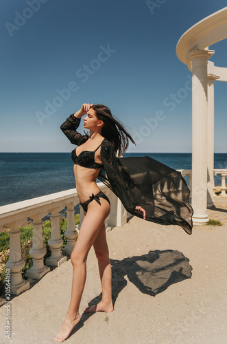 Foto Murales sexy woman with dark hair in luxurious bikini relaxing on the beach