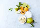 Fresh Ingredients for a Vegan Smoothie ( apricots, banana, pear, lime, mint and almond milk) - 205654474