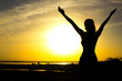 Leinwanddruck Bild - silhouette of a girl raising hands to the sky after physical training, a woman enjoying the sunset