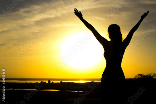 Leinwanddruck Bild silhouette of a girl raising hands to the sky after physical training, a woman enjoying the sunset