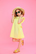 Quadro Trendy curly girl in dress and sunglasses wearing straw hat posing on pink.