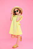 Trendy curly girl in dress and sunglasses wearing straw hat posing on pink.