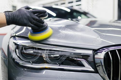 Leinwandbild Motiv Car detailing - Worker with orbital polisher in auto repair shop. Selective focus.