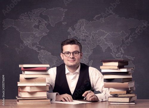 Foto Murales A young ambitious geography teacher in glasses sitting at classroom desk with pile of books in front of world map drawing on blackboard, back to school concept.