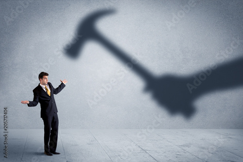 Leinwanddruck Bild Business person afraid of a shadow hand holding hammer concept on background