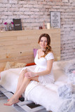 Pregnant happy woman holding belly and sitting on bed in bedroom, wearing white dress. Concept of motherhood and interior.