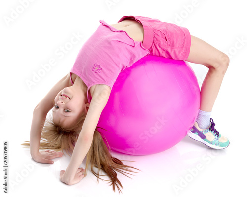 little girl doing exercises on a big ball for fitness.