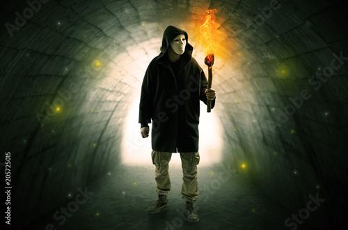 Brzydki mężczyzna z płonącym flambeau odprowadzeniem w ciemnym tunelu